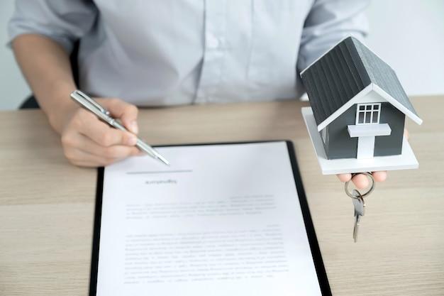 Рука агента по недвижимости, держащая ручку, указывает на деловой договор, аренду, покупку, ипотеку, ссуду, страхование жилья.
