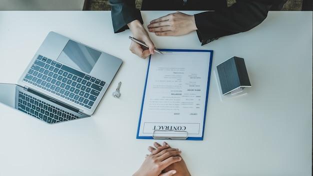 Агент по недвижимости держит ручку и объясняет деловой договор или страхование жилья