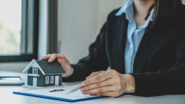 Агент по недвижимости рука держит ручку и объясняет деловой договор или страхование жилья