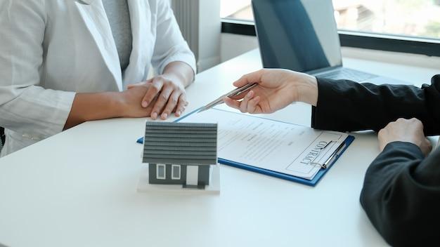 Агент по недвижимости держит ручку и объясняет деловой договор, аренду, покупку, ипотеку, ссуду или страхование жилья.