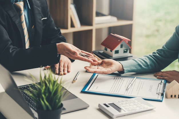 Real estate agent hand over the house keys to the customer for a house sale agreement the contract was signed at the office.