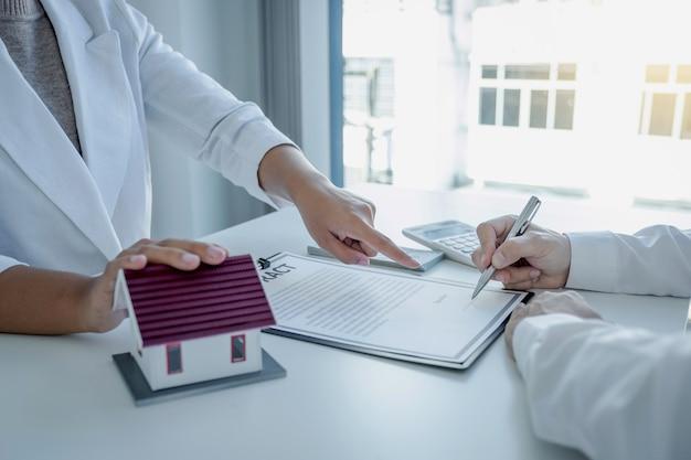 Рука агента по недвижимости указывает и объясняет деловой договор или страхование жилья покупателю-мужчине