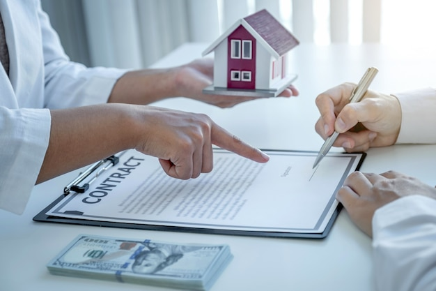 The real estate agent hand pointing and explains the business contract to the man buyer.