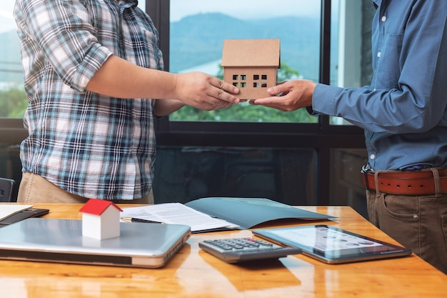 Real estate agent handing over a house model with his client after sealing deal
