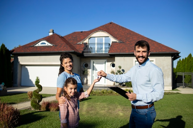 Real estate agent handing over keys of the new house to the single mother with her child.