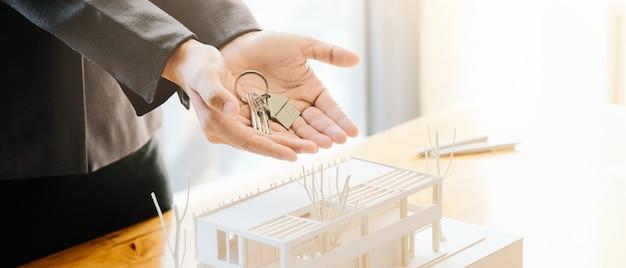 不動産業者は、承認された住宅ローン申請書で家の鍵を渡し、ハンドシェイクを提供します