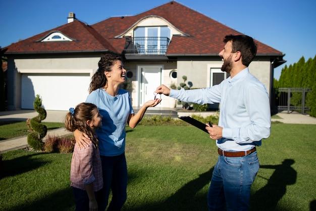 새 집의 열쇠를 아이가 있는 미혼모에게 넘겨주는 부동산 중개인.