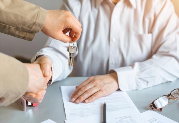 Агент по недвижимости держит ключ от дома к своему клиенту после подписания контракта. концепция недвижимости, бизнеса и недвижимости