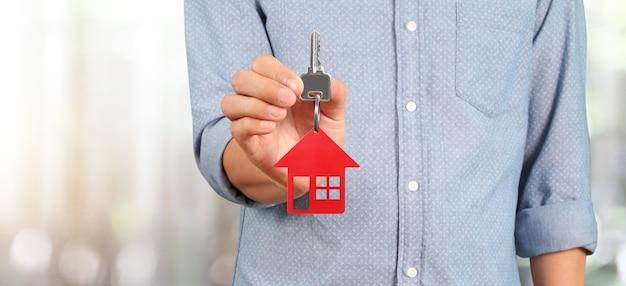 Агент по недвижимости держит ключ с крошечным красным домом