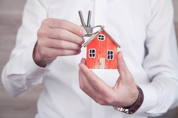 Real estate agent holding wooden house model and keys.