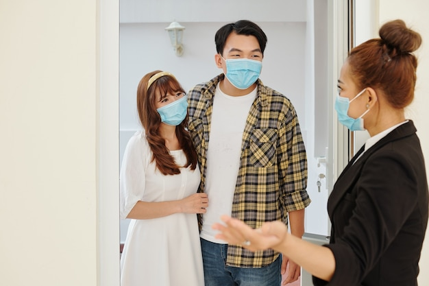 Real estate agent in medical mask opening door and inviting young couple in house on sale