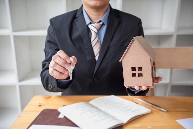 Агент по недвижимости предлагает дом и ключ. Premium Фотографии