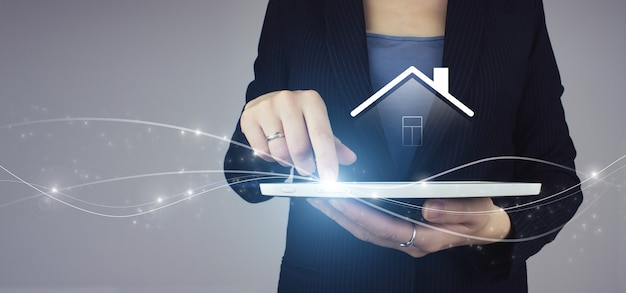 Real estate agent offer house, property insurance and security concept. white tablet in businesswoman hand with digital hologram house sign on grey. repair and renovation, maintenance services.