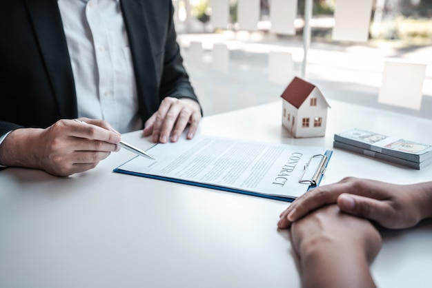 Real estate agent presenting home loan and giving house