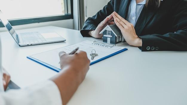 Агент по недвижимости препятствует подписанию контракта покупателем модели дома после того, как объясняет страхование дома