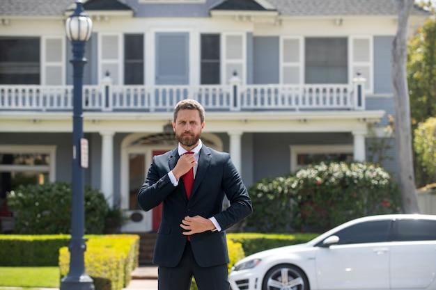 不動産。エージェントは家を売る準備ができています。現代の家の外に立っているビジネスマン。