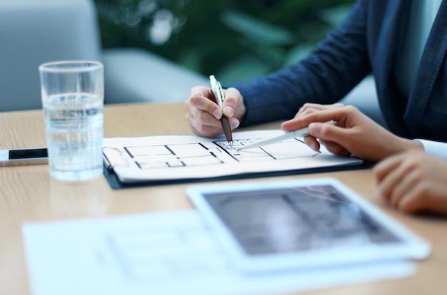 Агент по недвижимости показывает планы дома на электронном планшете