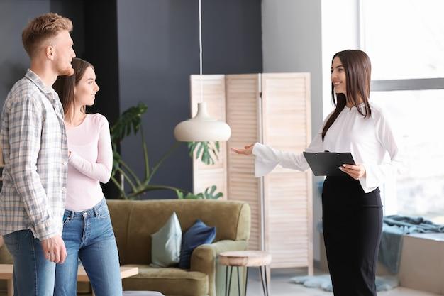 Агент по недвижимости показывает молодой паре новый дом