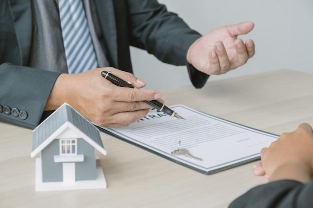 Агент по недвижимости подписывается с ключом от модели дома и объясняет деловой договор или страховку женщине-покупателю