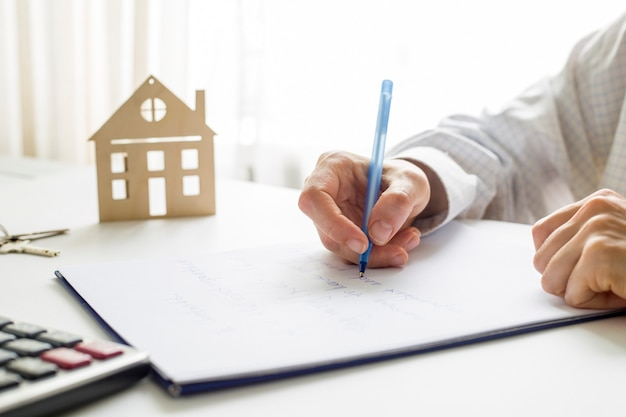 The real estate agent signs the document.