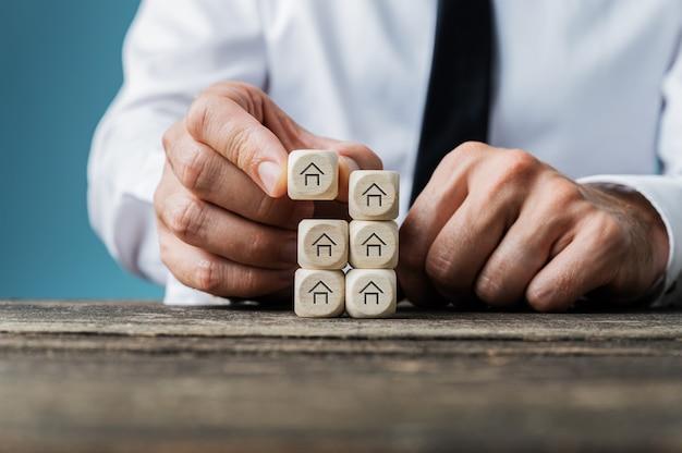 Агент по недвижимости укладывает деревянные кубики с формой дома на концептуальном изображении.