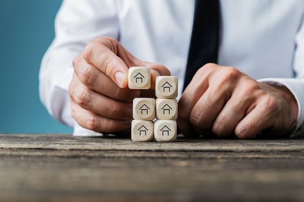Real estate agent stacking wooden dices with house shape on them in a conceptual image.