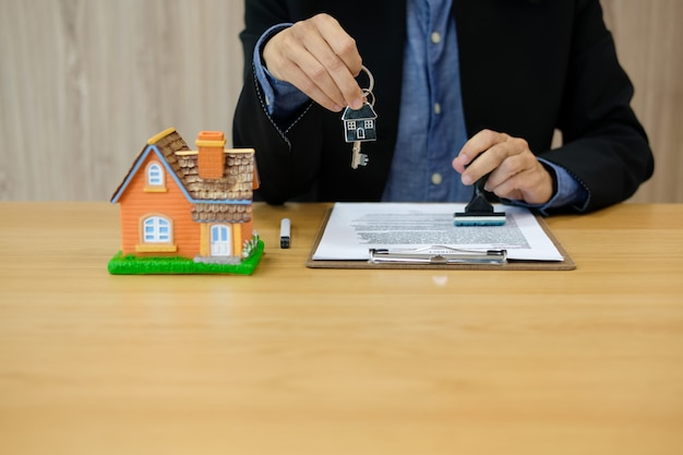 Real estate agent with house key stamping approved on mortgage loan contract agreement document