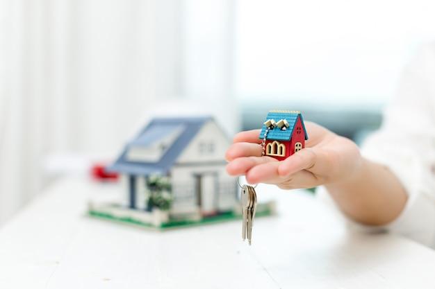 Агент по недвижимости с моделью дома и ключами