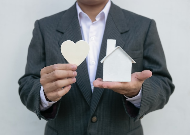 Real estate agent with house model and white heart
