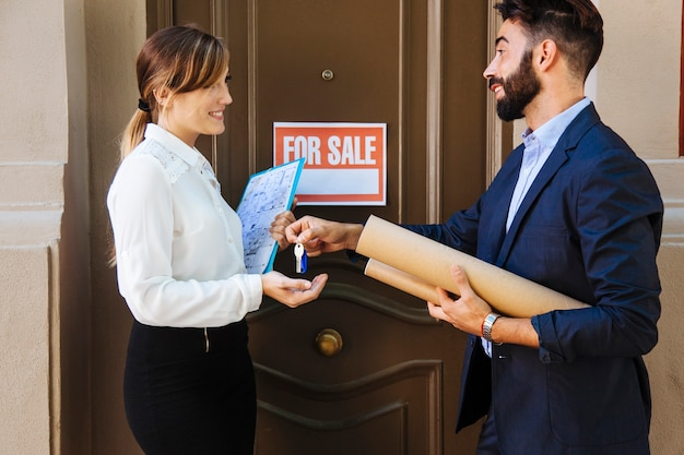 Real estate agent and woman interchanging keys