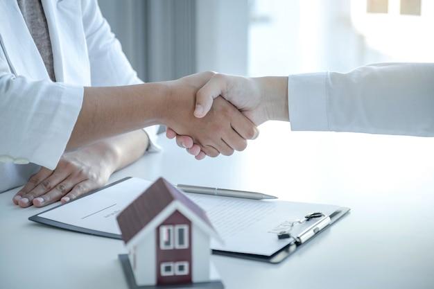 Рукопожатие агентов по недвижимости и покупателей после подписания бизнес-контракта об аренде, покупке ипотечного кредита или страховании жилья