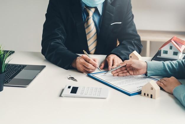 Агенты по недвижимости и клиенты занимаются продажей домов, договор был подписан в офисе.