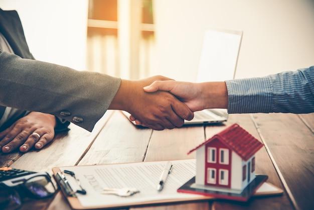 부동산 중개인과 고객이 손을 잡고 보험, 재산 양도 권에 대한 비즈니스 거래에 관한 계약 체결을 축하합니다.