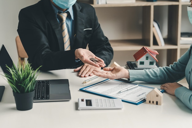 Real estate agents deliver house key to customers purchase and sale agreements contract document are completed at the office.