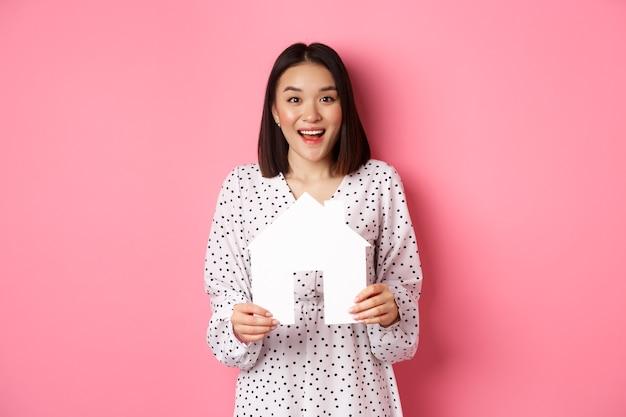 Недвижимость. пораженная азиатская женщина ищет квартиру, держит модель дома и счастлива смотрит в камеру, стоя над розовым