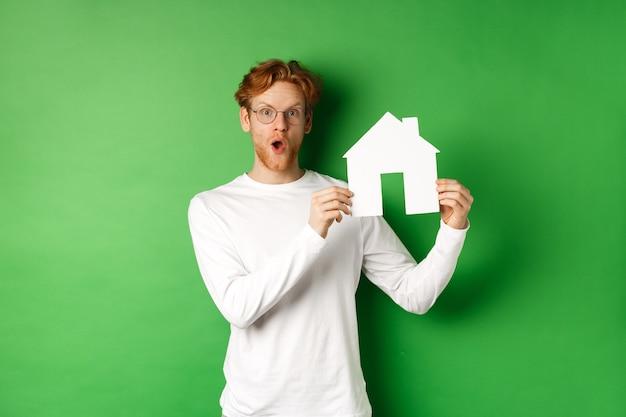 不動産と購入不動産のコンセプト。紙の家のモデルを示し、緑の背景の上に立って驚いて見える驚いた若い赤毛の男。