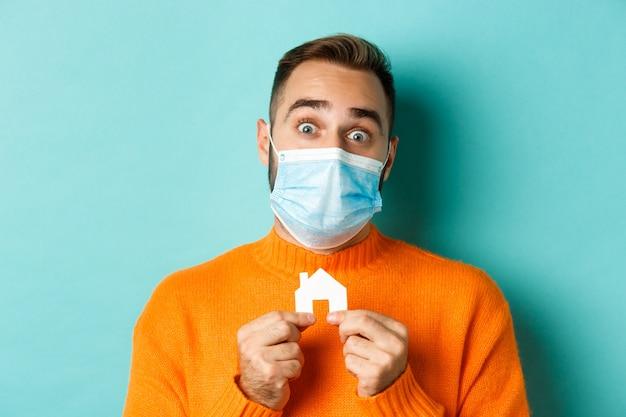 부동산 및 코로나 바이러스 전염병 개념. 작은 집을 들고 의료 마스크에 성인 남자의 클로즈업