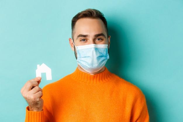 부동산 및 코로나 바이러스 전염병 개념. 작은 종이 집 maket를 들고 웃 고, 아파트, 밝은 파란색 배경에 대 한 검색 의료 마스크에 성인 남자의 클로즈업.