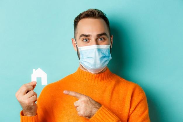 부동산 및 코로나 바이러스 전염병 개념. 집에서 가리키는 의료 마스크에 성인 남자의 클로즈업