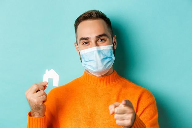 부동산 및 코로나 바이러스 전염병 개념. 당신을 가리키고 밝은 파란색 배경 위에 서있는 작은 종이 집을 보여주는 의료 마스크에 성인 남자의 클로즈업.