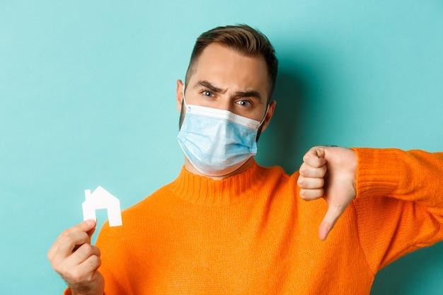 부동산 및 코로나 바이러스 전염병 개념. 작은 종이 집과 엄지 손가락 다운, 청록색 배경을 보여주는 얼굴 마스크에 실망 된 남자의 클로즈업.