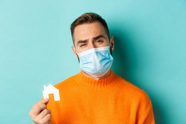 부동산 및 코로나 바이러스 전염병 개념. 밝은 파란색 배경 위에 서있는 얼굴 마스크와 찡그린 화가 찡그린 얼굴 마스크에 슬픈 남자의 클로즈업.