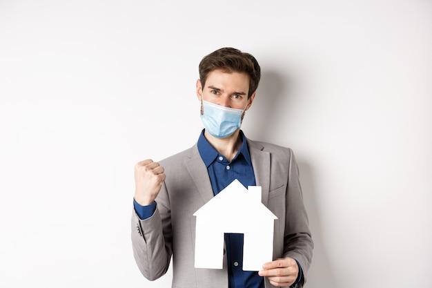 Недвижимость и концепция covid-19. взволнованный мужчина в медицинской маске и костюме, мотивированный на покупку дома, держит бумажный вырез дома и говорит да, на белом фоне.