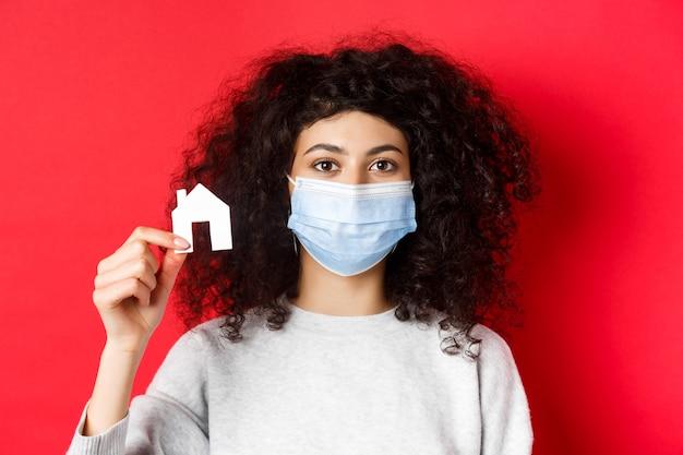 Недвижимость и концепция covid-19. возбужденная женщина в медицинской маске, показывающая небольшой вырез бумажного домика, стоящий на красном фоне.