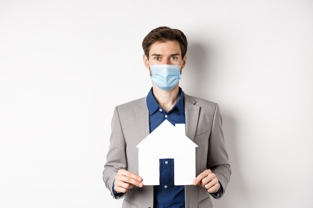 부동산 및 covid-19 개념. 의료 마스크와 양복 종이 집 컷 아웃을 표시 하 고 카메라, 흰색 배경보고 세일즈 맨.