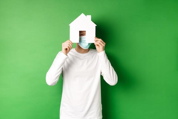 부동산 및 covid-19 전염병 개념. 얼굴 마스크를 쓴 재미있는 청년과 종이 집 컷아웃 뒤에 흰색 긴팔 숨은 얼굴, 카메라 엿보기, 녹색 배경