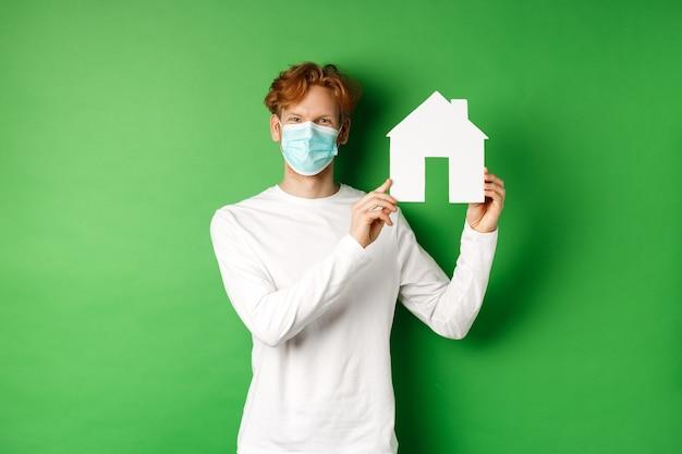 부동산 및 covid-19 유행성 개념. 종이 집 컷 아웃을 보여주는 녹색 배경 위에 서 눈으로 웃 고 의료 마스크에 젊은 빨간 머리 남자.