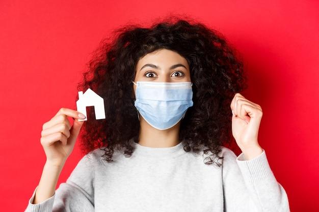 Концепция недвижимости и covid возбудила женщину в медицинской маске, демонстрирующую вырез из небольшого бумажного домика ...