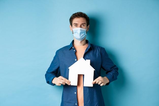 부동산 및 covid 개념. 얼굴 마스크에 행복 한 젊은 남자가 카메라, 파란색 배경에 놀란 찾고 종이 집 컷 아웃을 보여줍니다.