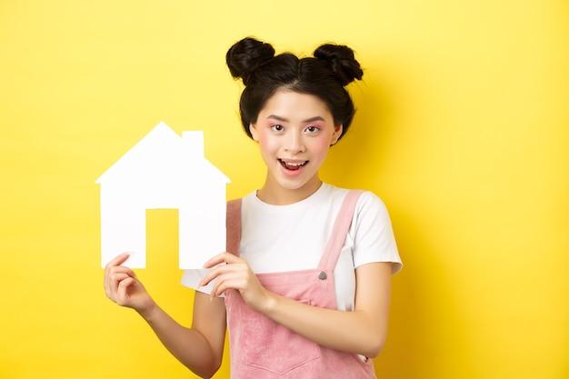 不動産と家族の概念。明るい化粧とスタイリッシュなヘアバン、紙の家の切り欠きを示す、決心した笑顔、黄色のかわいいアジアの女性